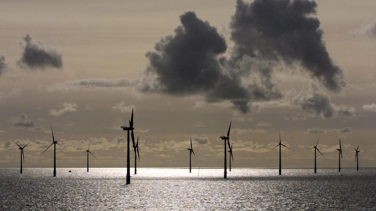 Des éoliennes dans l'eau photographiées en contre-jour sous un ciel nuageux couleur sépia