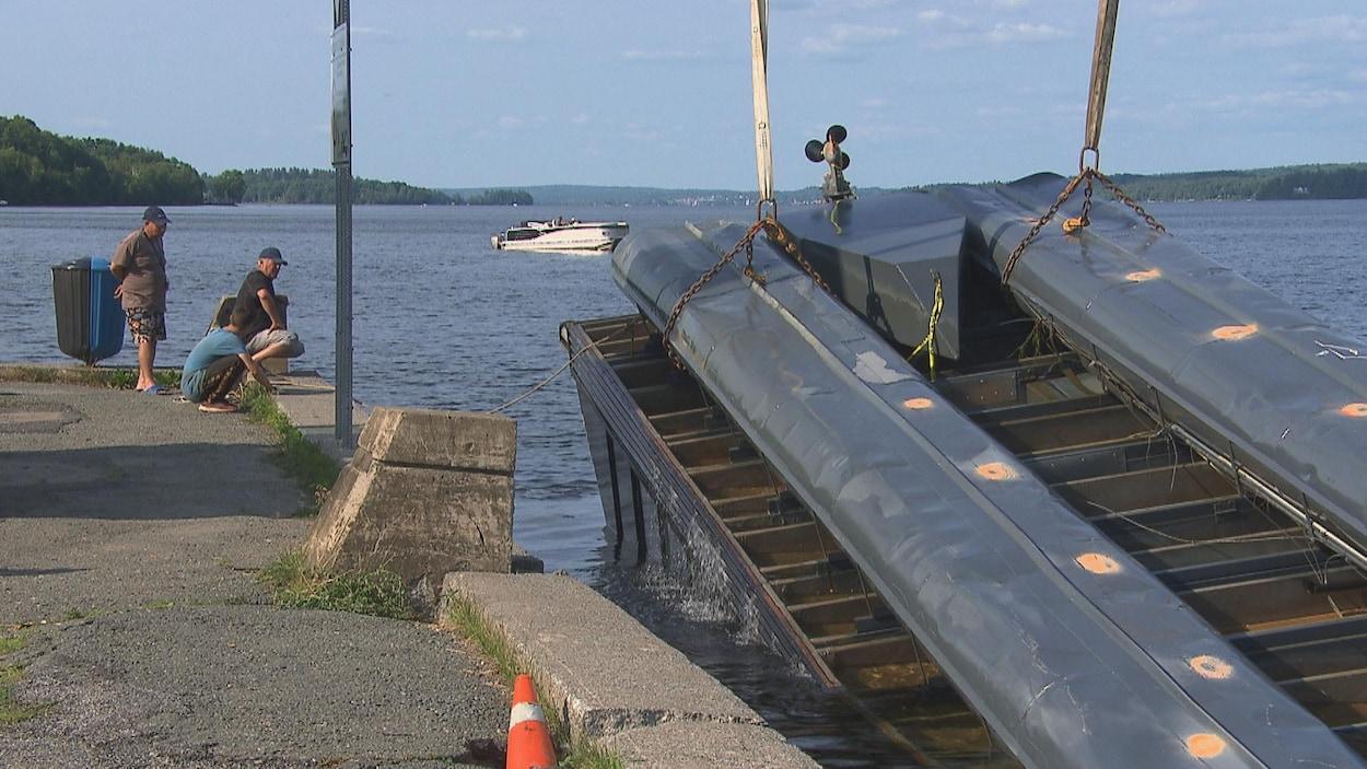 L'épave est maintenue par une grue aux abords du quai.