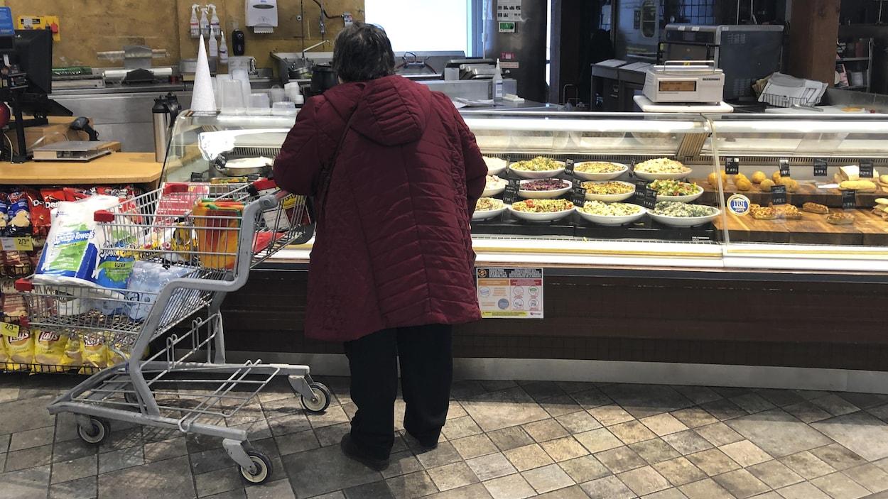 Une femme accoté sur son chariot devant un comptoir dans un magasin d'alimentation.