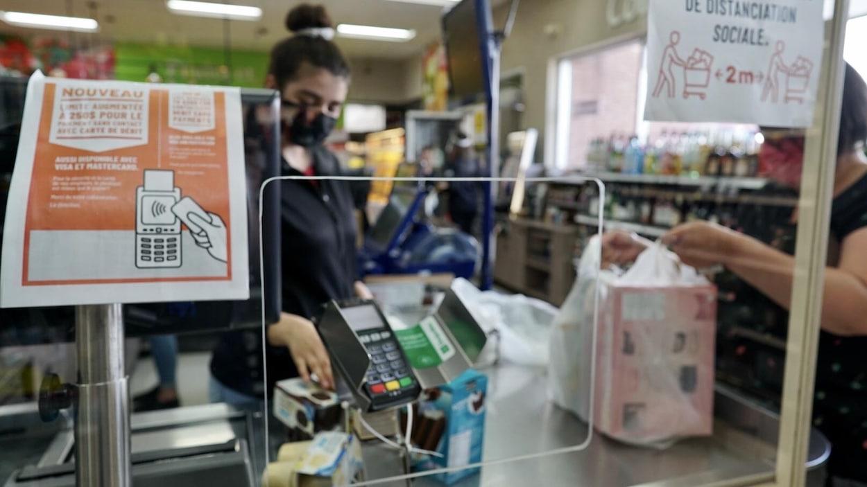 Une caissière fait payer une client à travers un plexiglas.