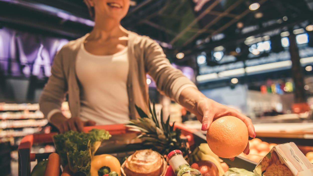 Une femme pousse un panier d'épicerie rempli de légumes et de fruits.