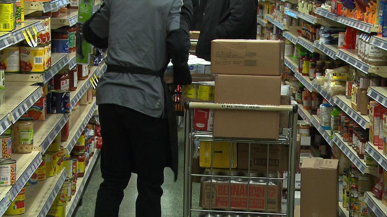 Un employé remplissant les tablettes d'une épicerie.