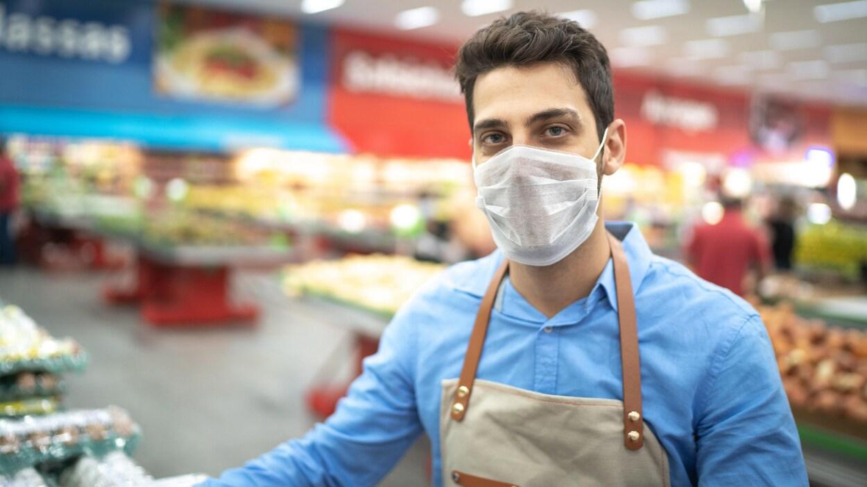 Un travailleur dans une épicerie porte un masque.