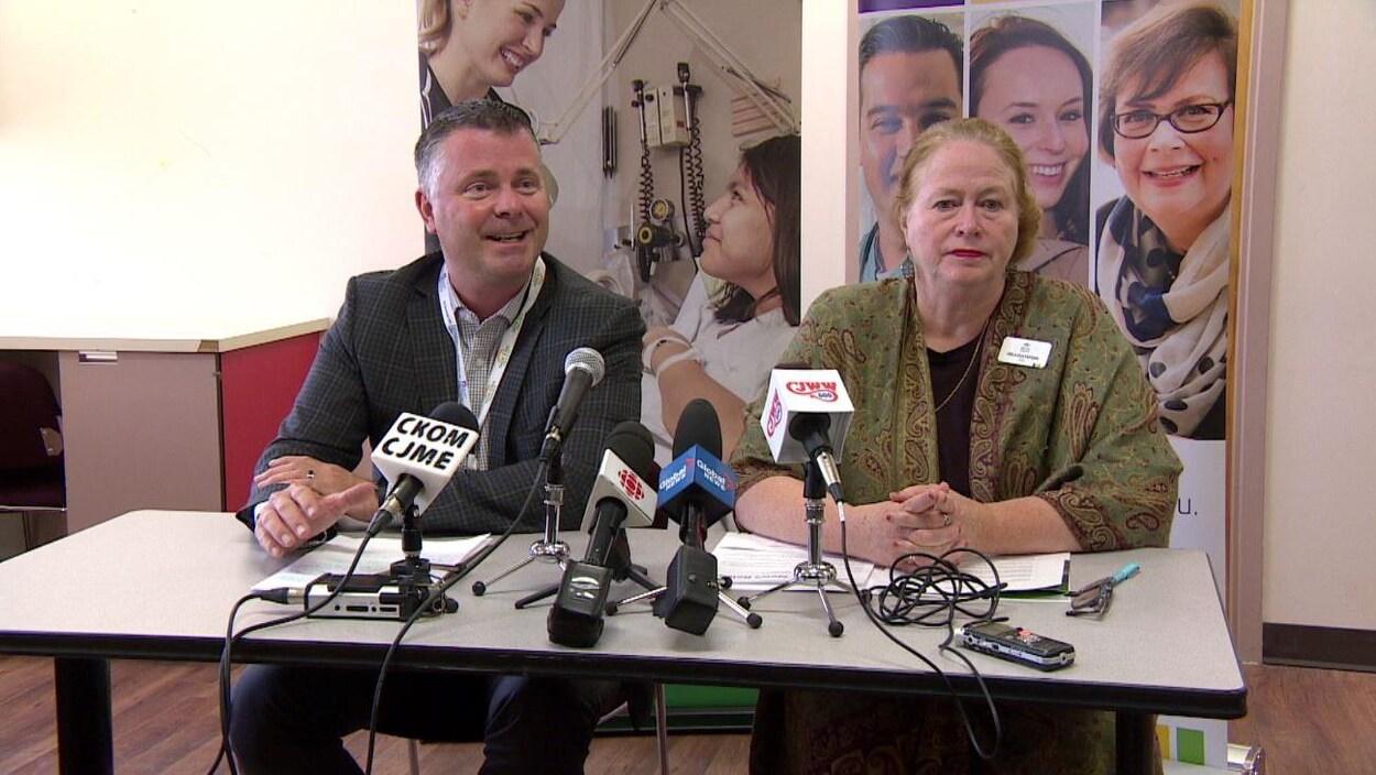 Corey Miller et Arla Gustafson sont assis à une table où sont posés des microphones et ils répondent aux questions des journalistes.