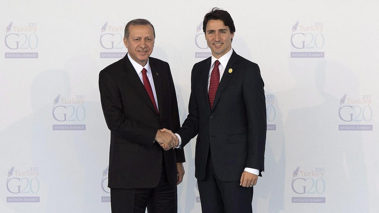 Justin Trudeau et Recep Tayyip Erdogan se serrent la main.