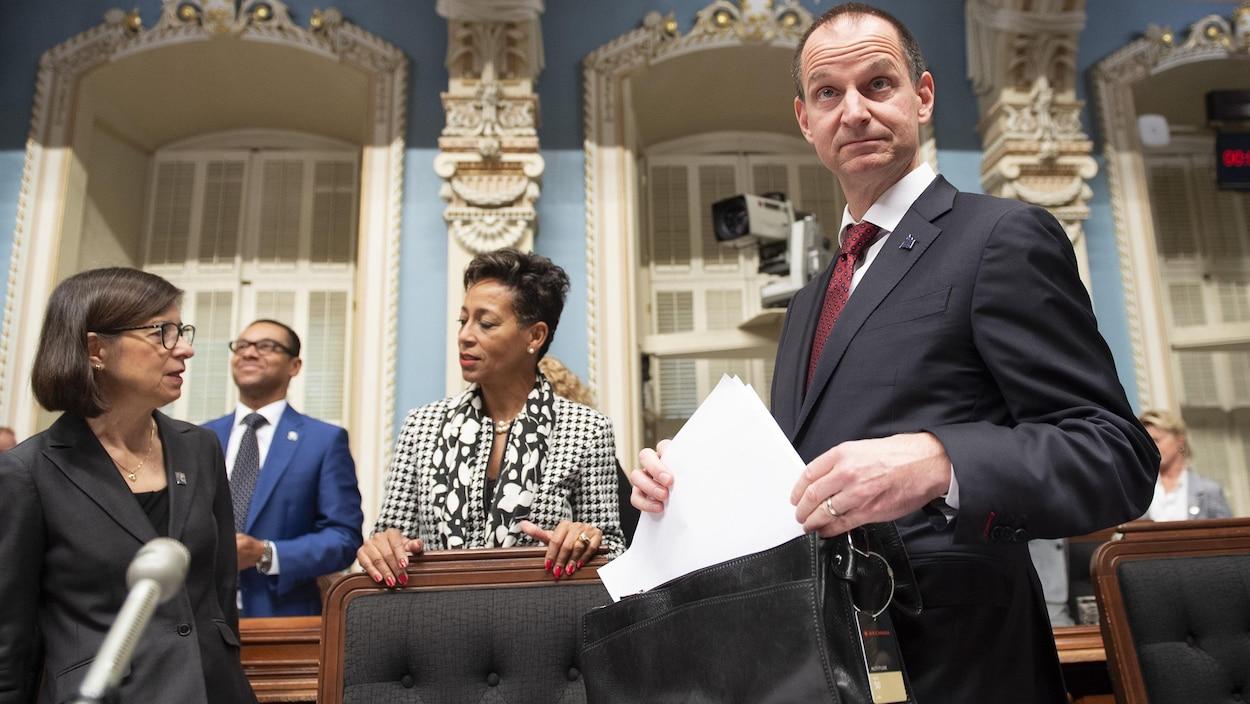 Eric Girard range des documents dans sa serviette au Salon bleu de l'Assemblée nationale.
