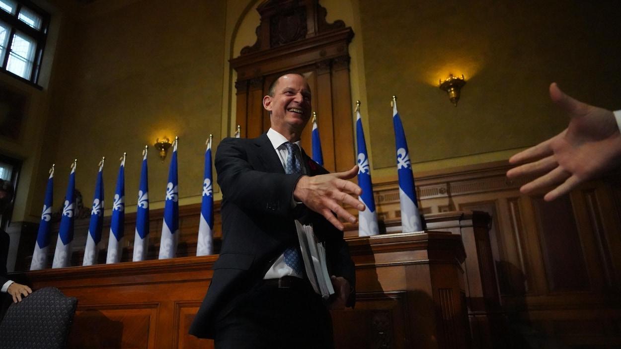 Eric Girard devant une enfilade de drapeaux du Québec.