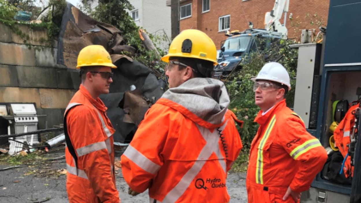 Trois hommes en combinaison orange discutent devant des débris.