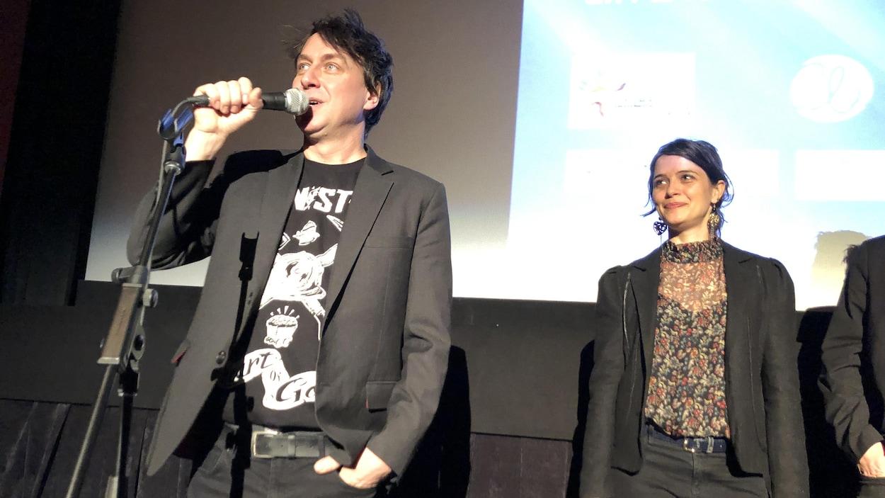 Éric Morin parle au micro dans une salle de cinéma, la comédienne Catherine de Léan à ses côtés.