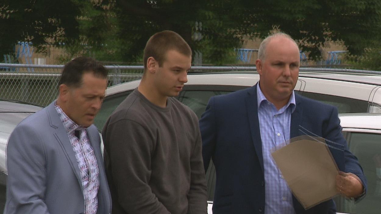 L'accusé entouré de deux hommes dans le stationnement du palais de justice