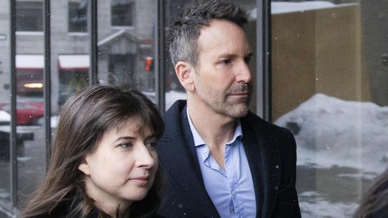 Éric Salvail, dehors, entre au palais de justice avec une jeune femme à ses côtés.