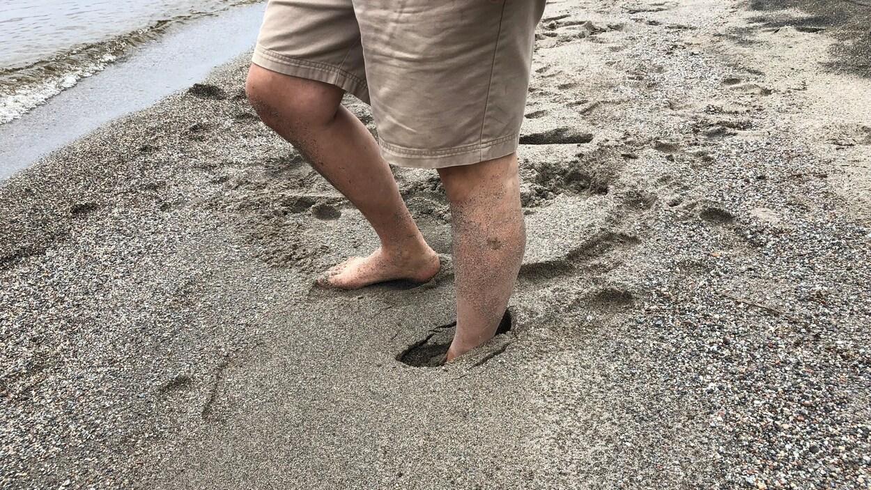 Un pied enlisé dans le sable.