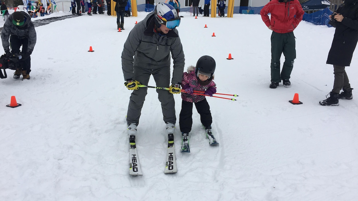 Un homme et une fille tiennent des bâtons de ski pour descendre une piste