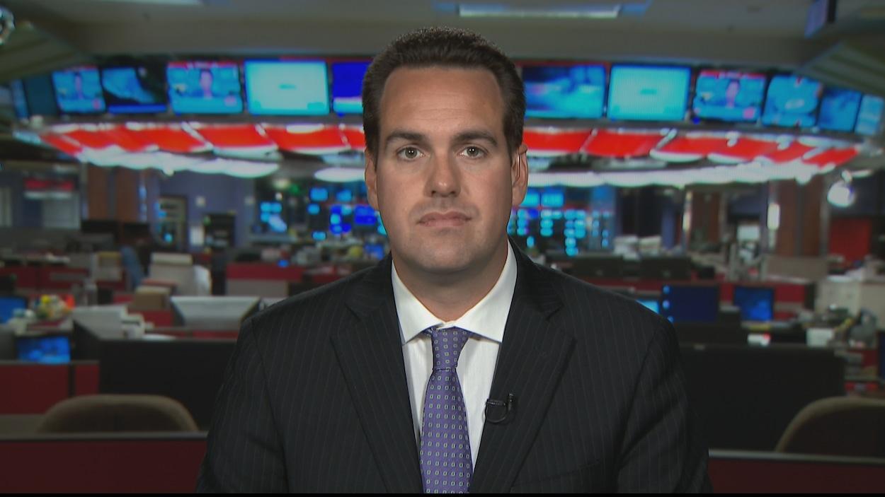 Un homme de face, la bouche fermée, devant une salle des nouvelles en arrière-plan