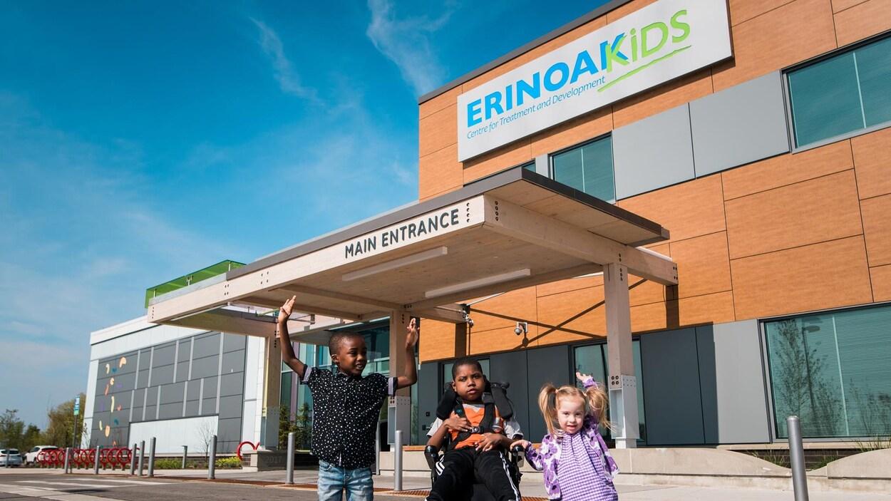 Trois enfants devant l'entrée principale du centre ErinoakKids.