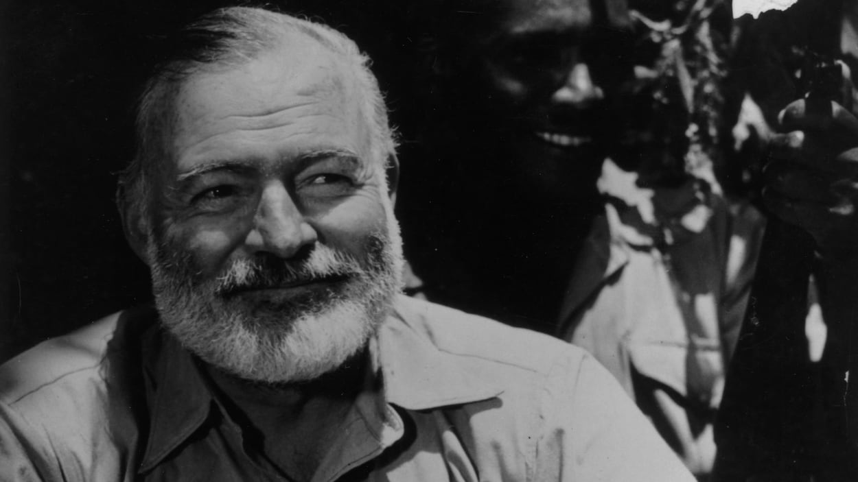 Assis, Ernest Hemingway sourit. Derière, on distingue un homme noir vêtu d'un chapeau.