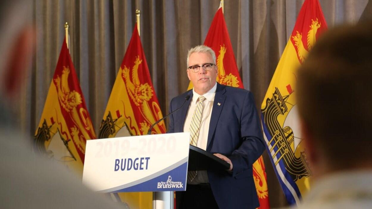 Ernie Steeves devant un lutrin sur lequel le mot « Budget » est écrit.