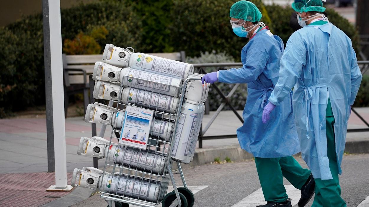 Deux travailleurs de la santé, portant des masques de protection, transportent des bouteilles d'oxygène sur un chariot.