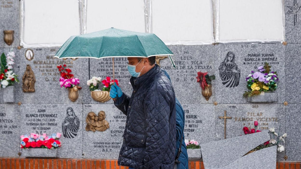 Un homme portant un masque se rend dans un cimetière de Madrid pour assister aux funérailles d'une personne atteinte par la COVID-19.