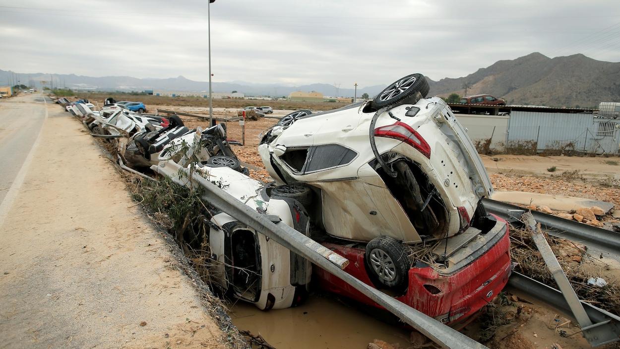 Des voitures balayées par les flots se retrouvent empilées sur le bord de la route.