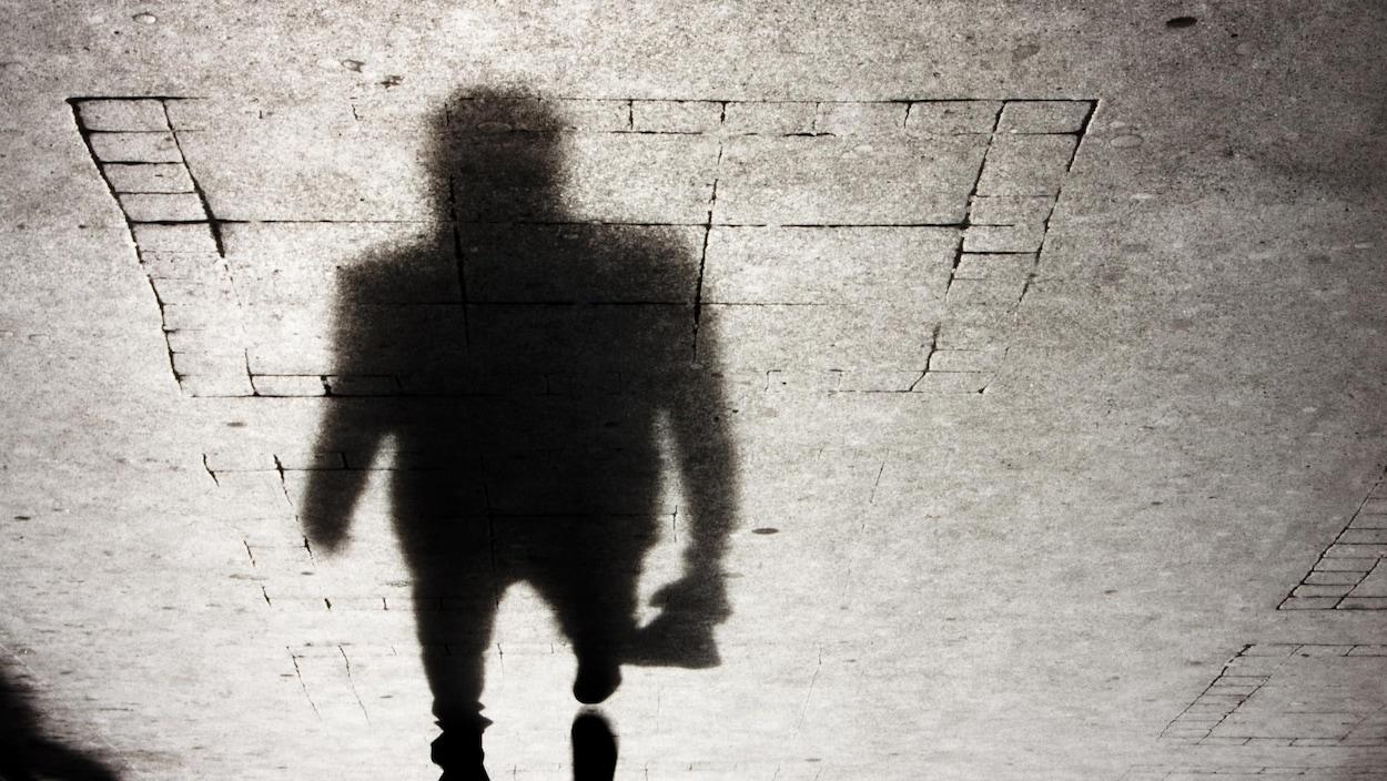 L'ombre d'une personne qui marche sur un trottoir la nuit.