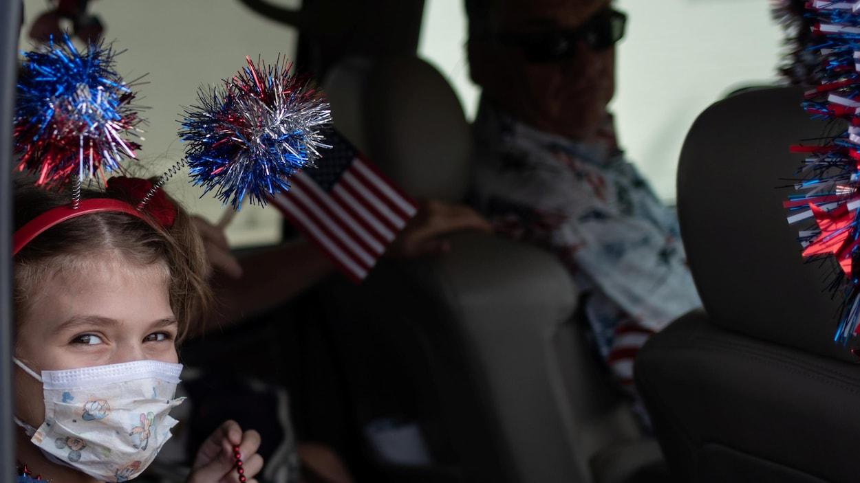 Une petite fille porte des décorations aux couleurs des États-Unis sur sa tête, mais aussi un masque sur son visage.