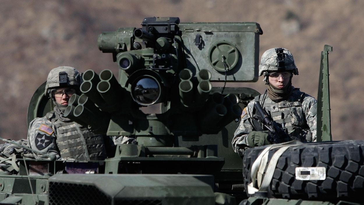 Deux soldats américains à bord d'un tank lors d'un exercice militaire.