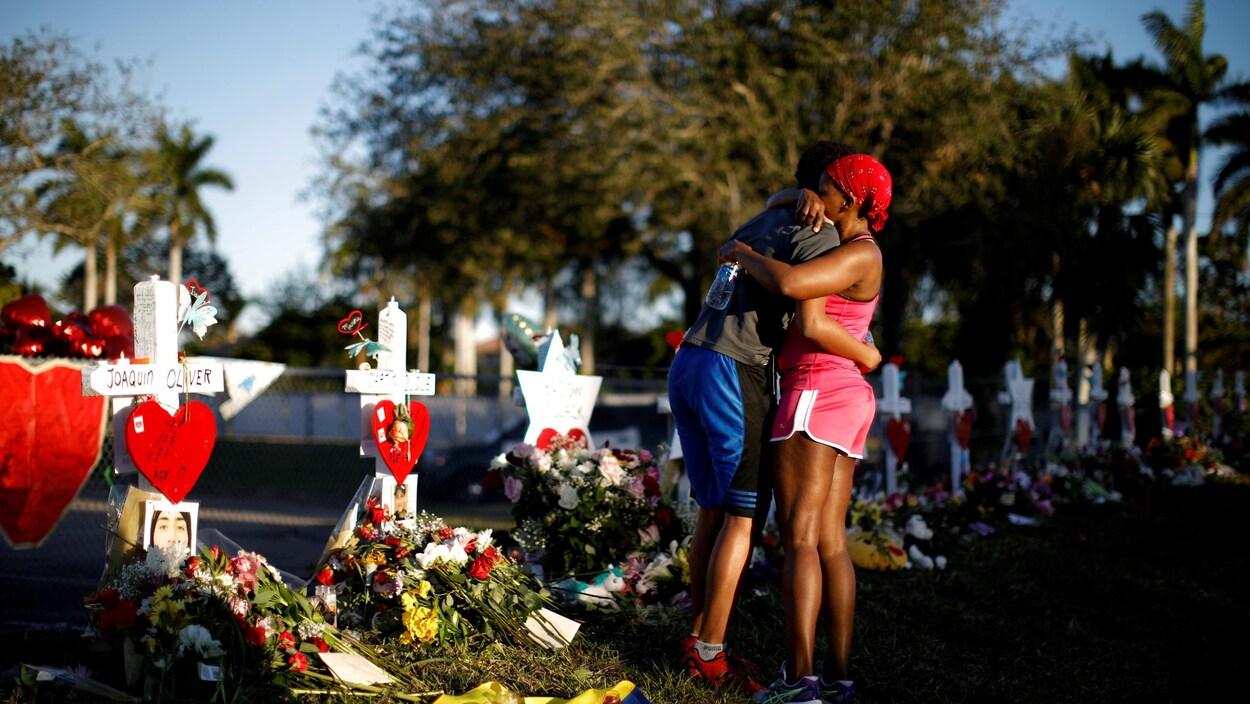 Un élève de l'école secondaire Parkland prend sa mère dans ses bras, près d'un mémorial aux victimes de la tuerie.