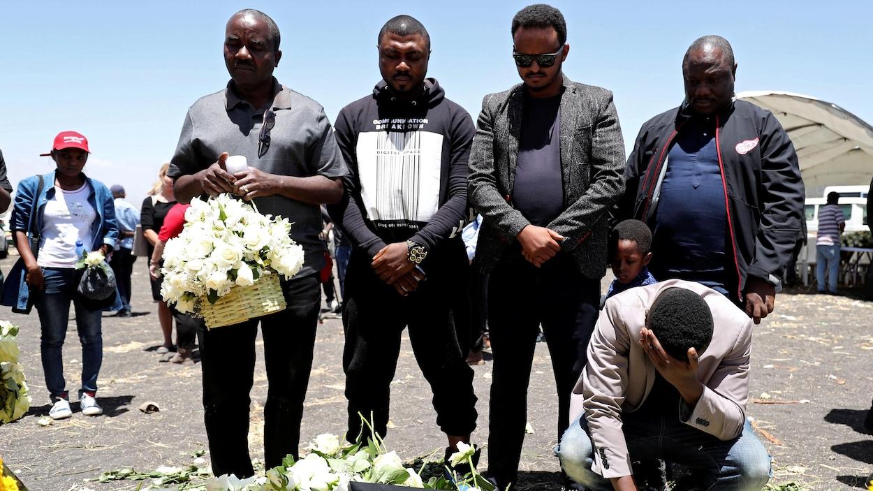 Des gens se recueillent devant des fleurs et des photos.