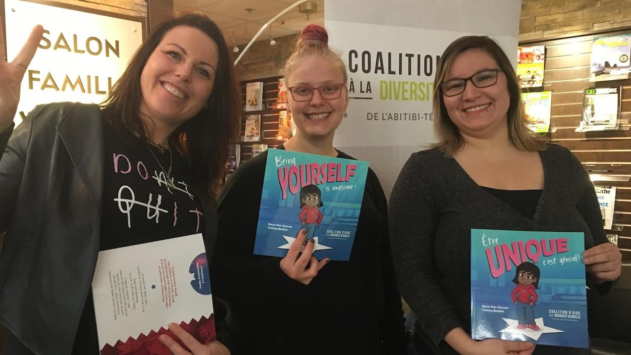 Marie-Pier Giasson, Marie-Aimée Fortin-Picard et Johanie Vendette sourient en tenant l'album  «Être unique, c'est génial».