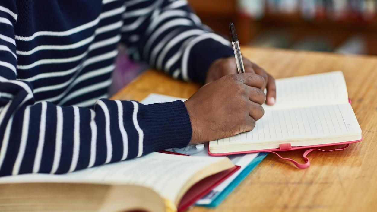 Un homme non identifié prend des notes dans un cahier.