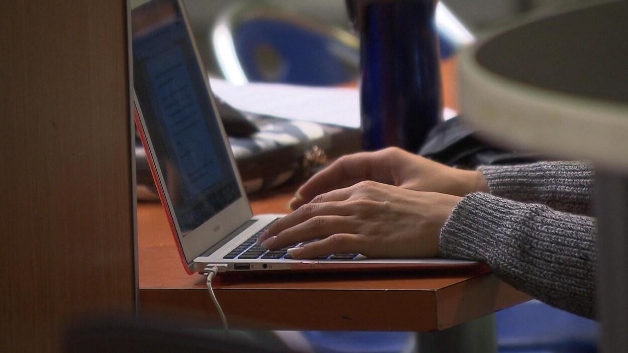Gros plan sur les mains d'une étudiante qui écrit sur un portable.