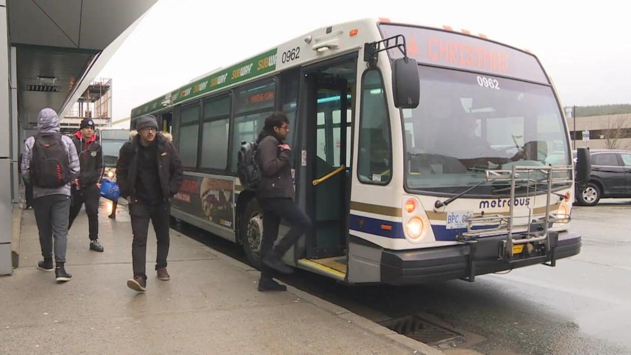 Des étudiants montent et descendent d'un autobus municipal à un arrêt.