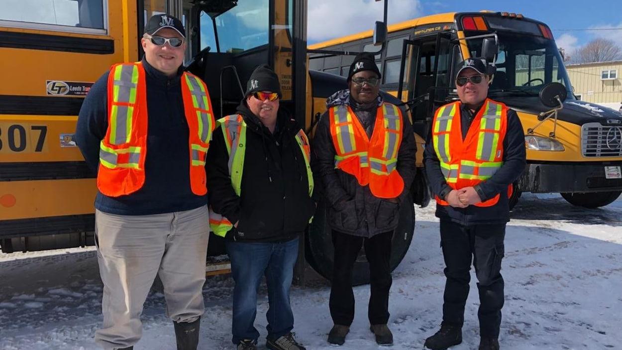Quatre hommes souriants debout devant des autobus scolaires