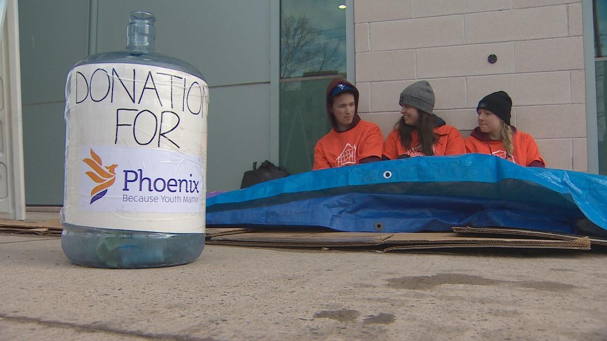 Trois étudiants dans la rue sous des toiles de plastique et des feuilles de carton