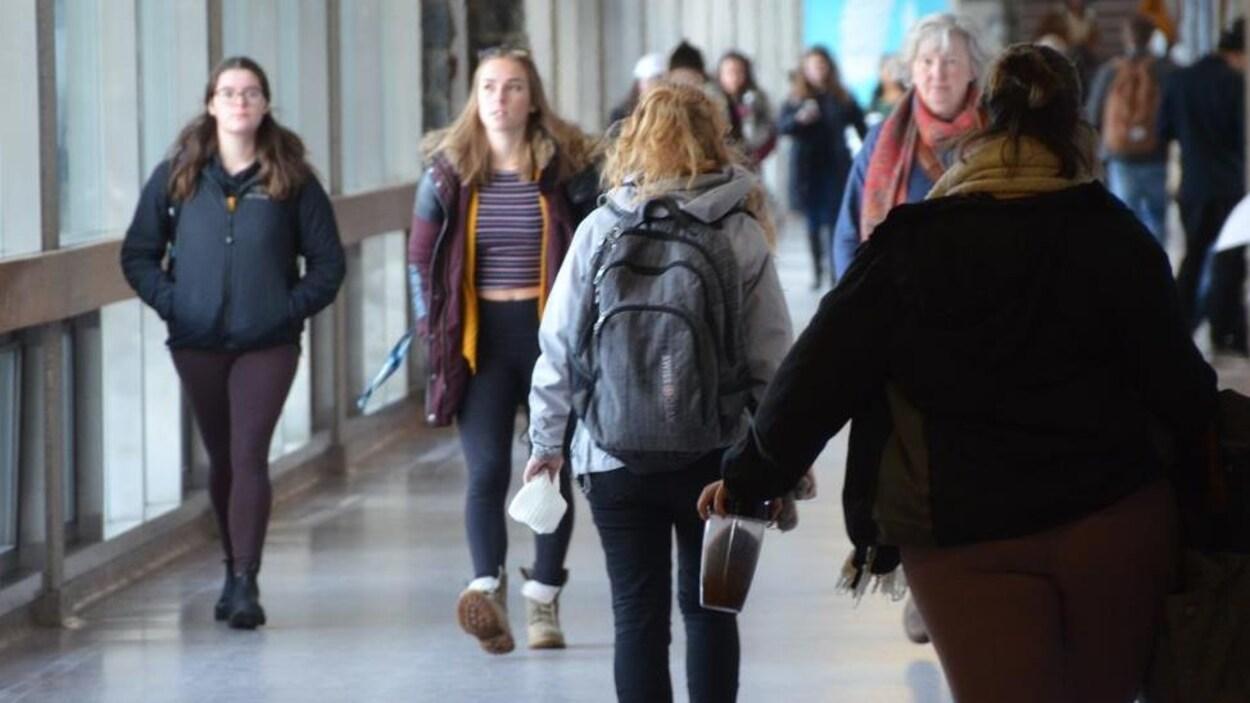 Des étudiants qui marchent dans un corridor.