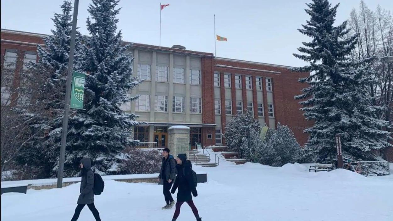 Trois personnes marchent dans la neige devant un édifice de l'Universtié de l'Alberta.