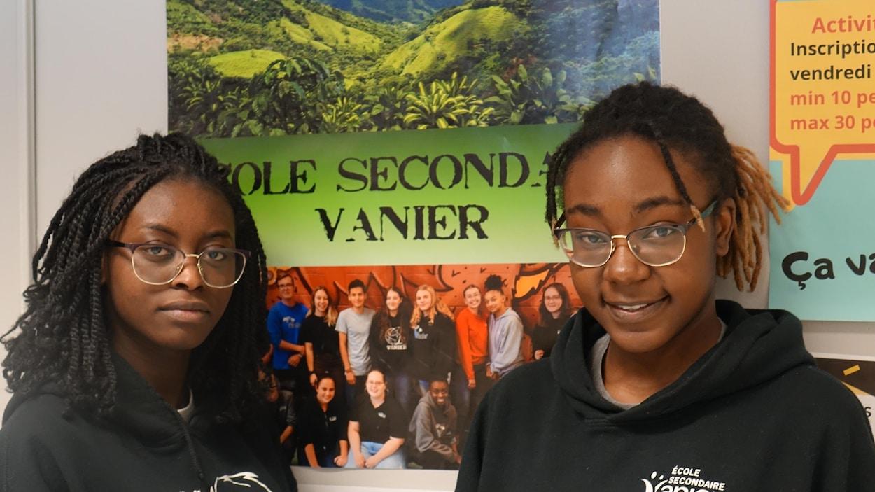 Eunice et Delphine Banza devant une affiche de l'école secondaire Vanier qui prépare un voyage humanitaire au Costa Rica.