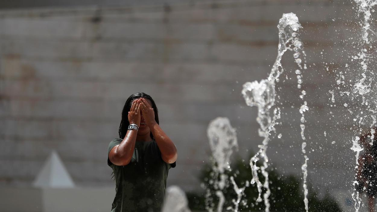 Une femme se rafraîchit dans une fontaine publique.