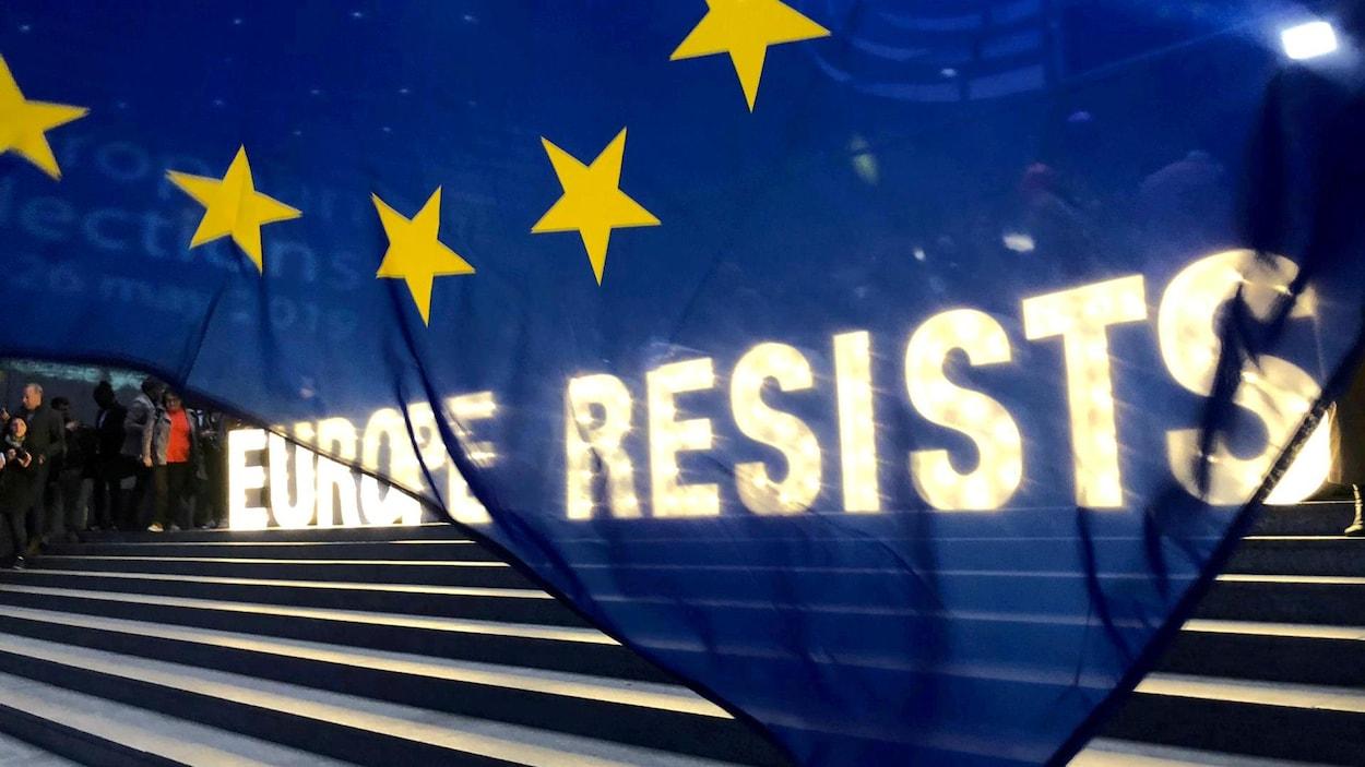 Un drapeau européen devant une inscription lumineuse « Europe resists », soit « l'Europe résiste »