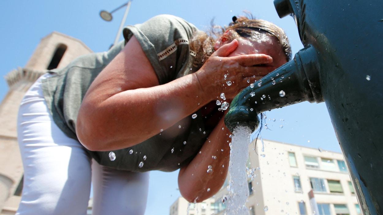 Une femme s'asperge le visage d'eau.