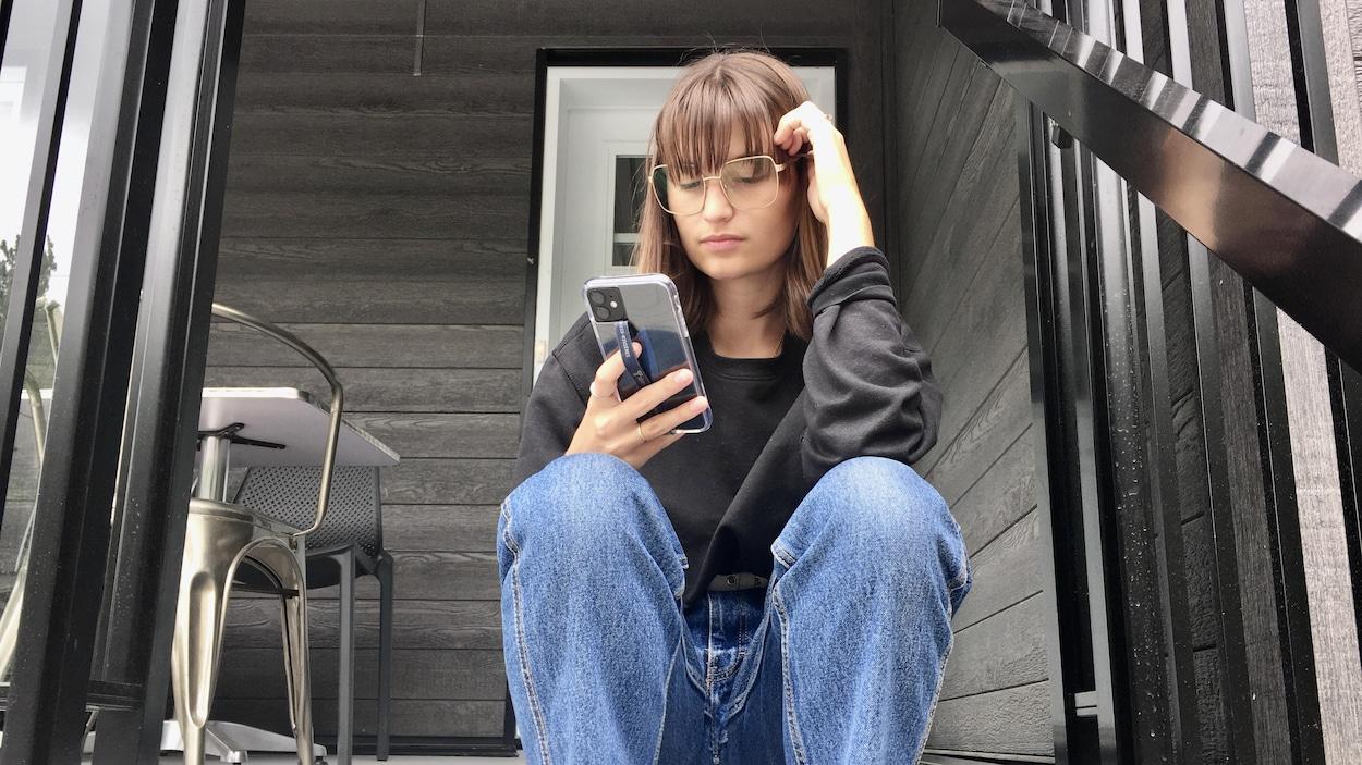 Un femme est assise dans les escaliers devant une maison et regarde son cellulaire.