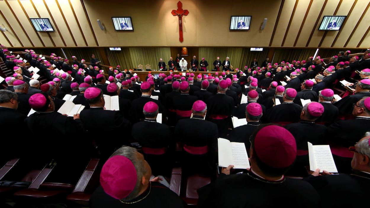 Des évêques sont assis dans un auditorium.