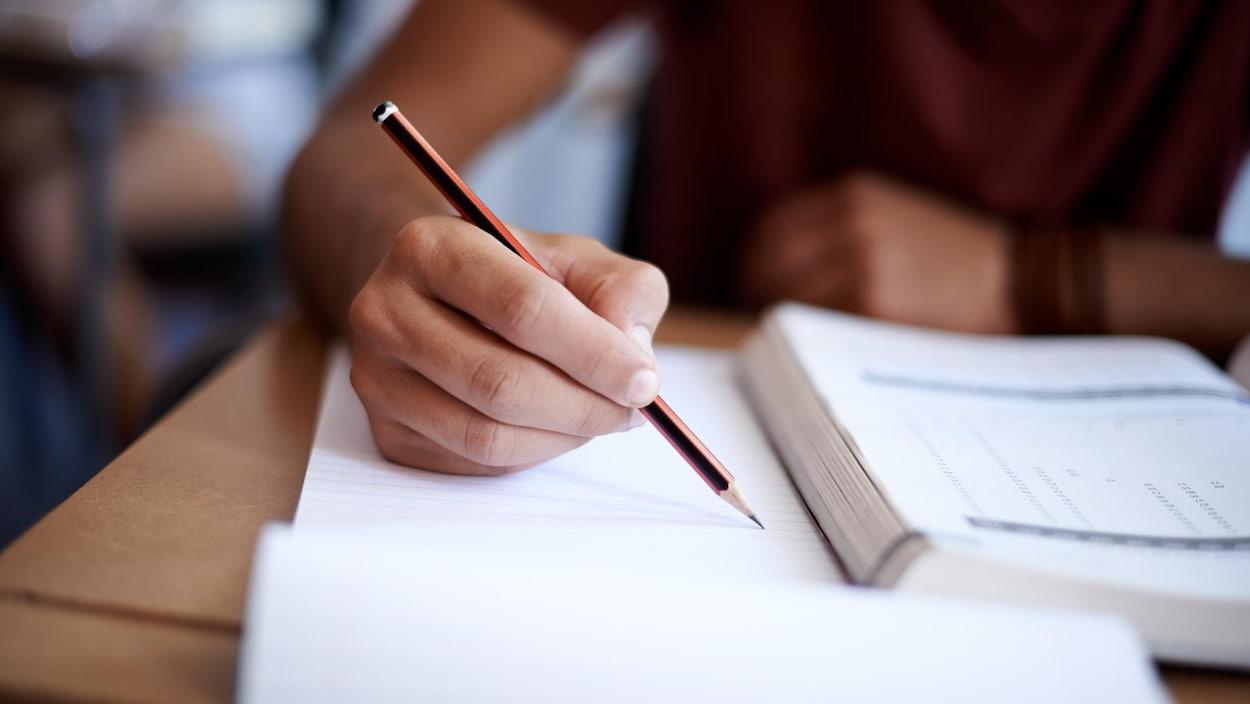 Main d'un étudiant qui prend des notes dans une classe