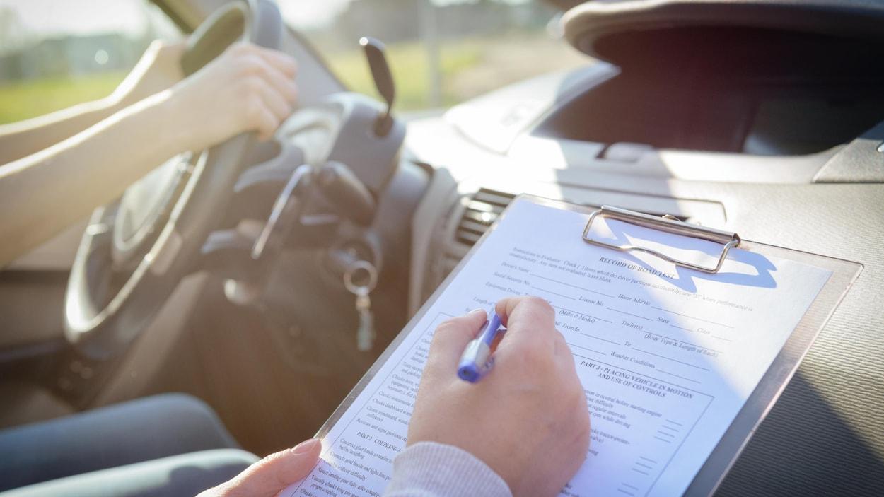 Un évaluateur prend des notes durant un examen de conduite.