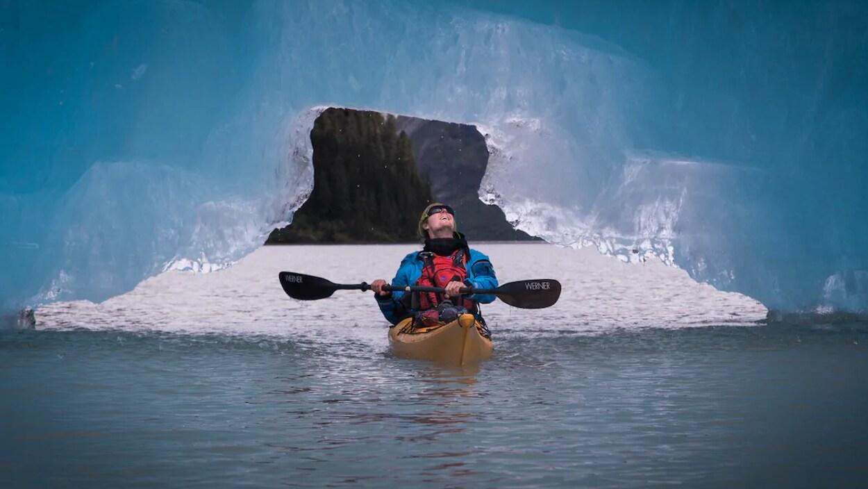 Un homme sur un kayak la tête versée vers l'arrière pour regarder la glace au-dessus de lui.