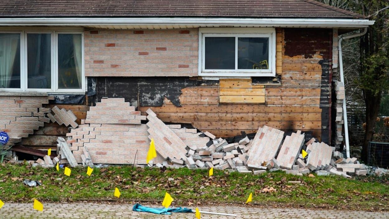 Façade d'une maison endommagée. Des briques sont sur le sol.