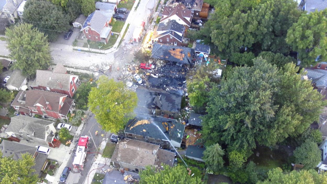 Photo des décombres d'une maison complètement démolie et de maisons adjacentes aux toits brûlés ou endommagés; un jet d'eau arrose l'un de ces toits.