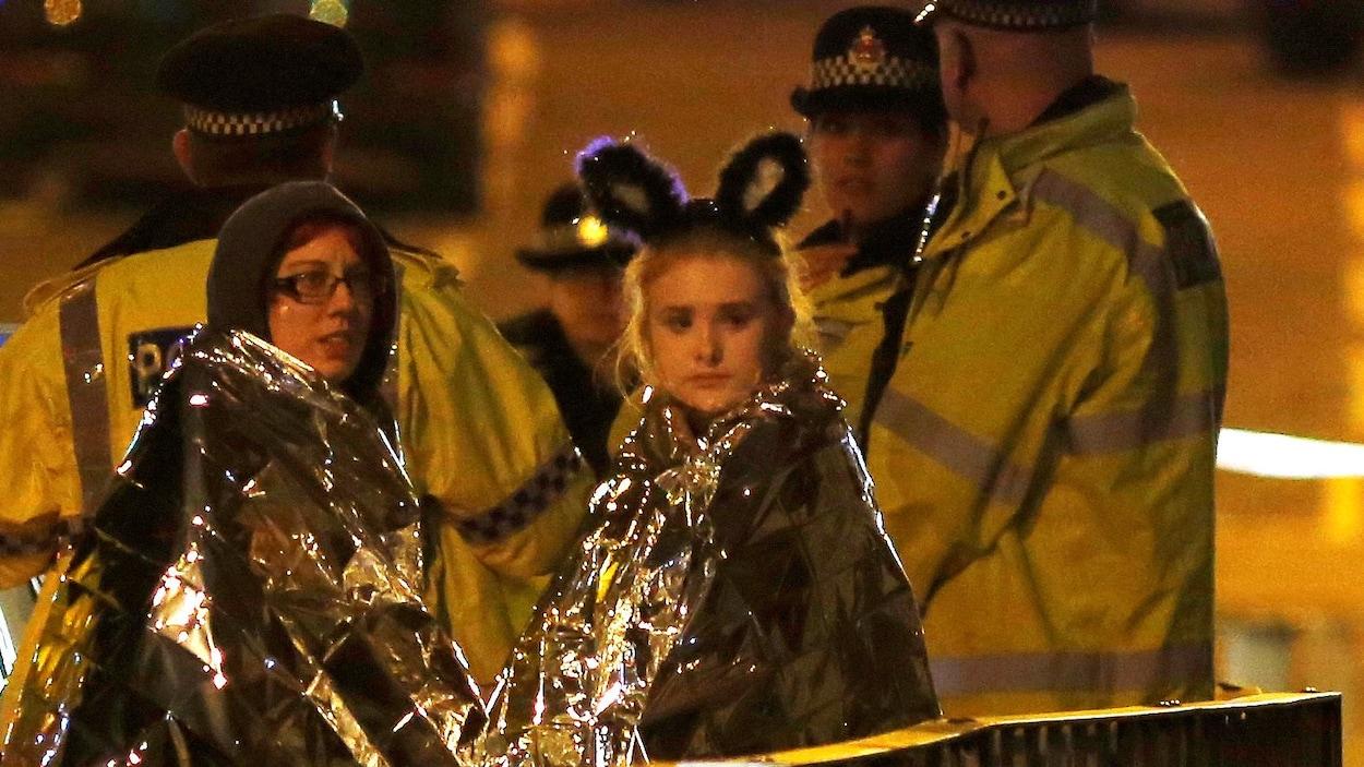 Deux jeunes femmes enveloppées dans des couvertures thermales à la sortie du Manchester Arena