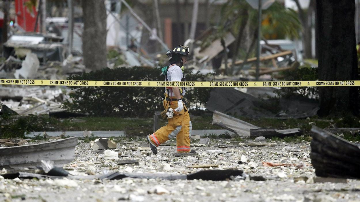 Un pompier marche dans les débris derrière un ruban « scène de crime ».